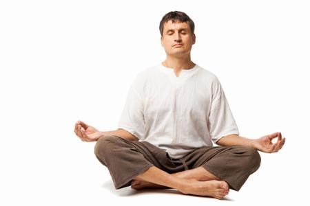 Hombre pacífico haciendo yoga y meditación - aislados en un fondo blanco