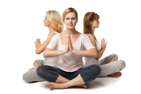 yoga meditation: Group of people relaxing and doing yoga in white studio Stock Photo