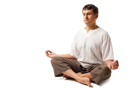 Peaceful man doing yoga and meditating - isolated over a white background photo