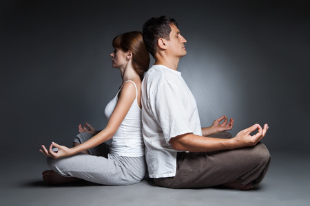 Young healthy couple in yoga position on dark background photo