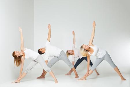 Groep van mensen ontspannen en het doen van yoga in witte studio Stockfoto - 27010708