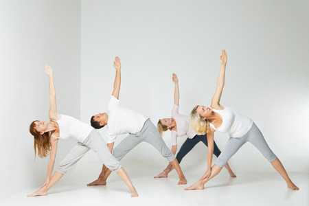 Group of people relaxing and doing yoga in white studio Stock Photo