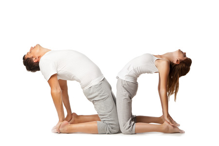 Young healthy couple in yoga position on white background photo