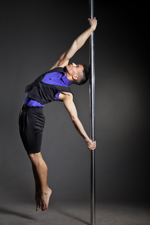 Young strong pole dance man over black background with flashes photo