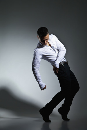 Modern style dancer posing on grey studio background photo