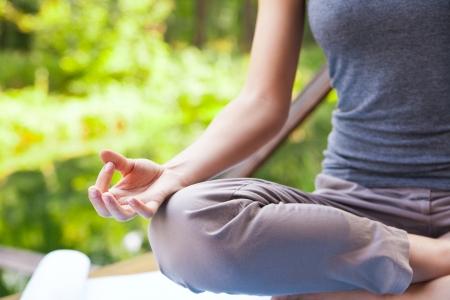 Jong meisje dat yoga (lotus houding) in het park Stockfoto