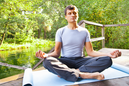 young man doing yoga (lotus pose) in the park photo
