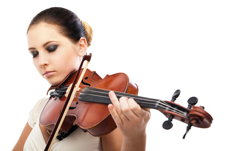 Beautiful young woman playing violin over white background photo