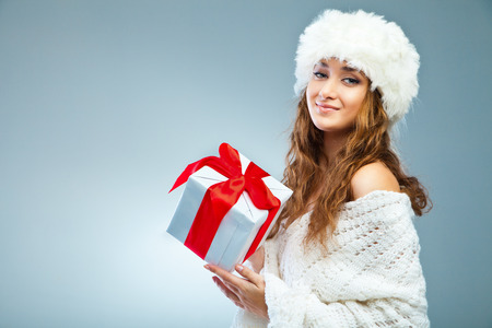 Young attractive girl in Christmas style holding present over grey photo