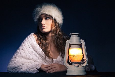 portrait of beautiful woman sitting with lantern over dark background photo