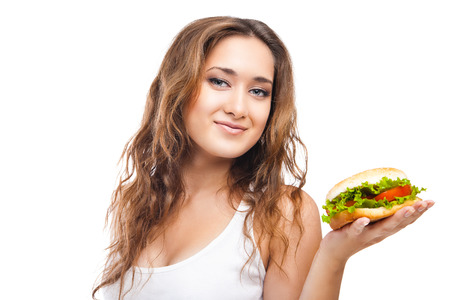 Happy Young Woman Eating big yummy Burger isolated on white background photo