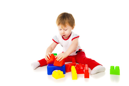 baby girl is playing with educational toys over white background photo