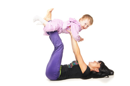 Yoga for woman and child. Mother with the baby doing exercises Standard-Bild