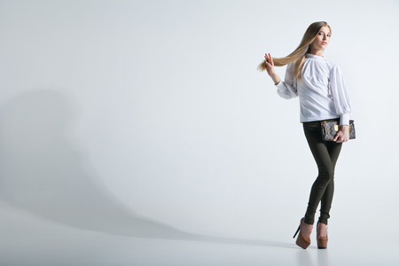 Full length casual young fashionable woman with a bag in light background