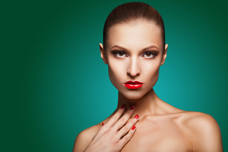 Close-up portrait of sexy caucasian young woman with red glamour make-up and bright manicure over green background photo