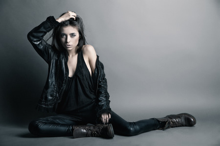 Fashion model wearing leather pants and jacket posing on grey background photo
