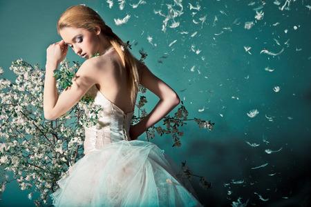 Porträtt av en kvinna i bröllopsklänning bakom grenar med blommor Stockfoto