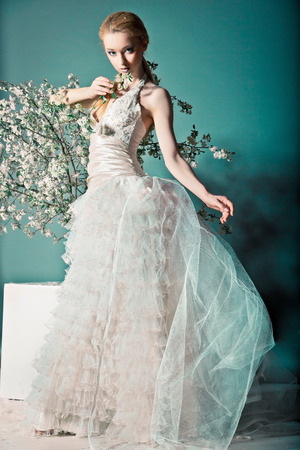 Portret van een vrouw in bruidsjurk achter de takken met bloemen