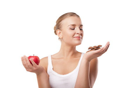 Doubtful woman holding an apple and chocolate trying to decide which one to eat on white background photo