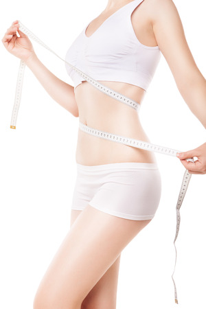 slimming woman measuring her thigh with measuring tape over white