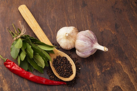 pepper in wooden spoon with garlic, bay leaves and chili pepper. Spices photo