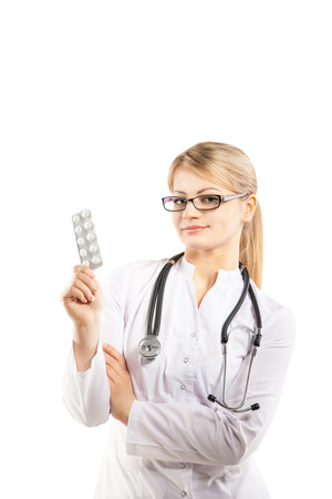 Doctor woman showing pill. Young female medical professional on white background Stock Photo - 27025061