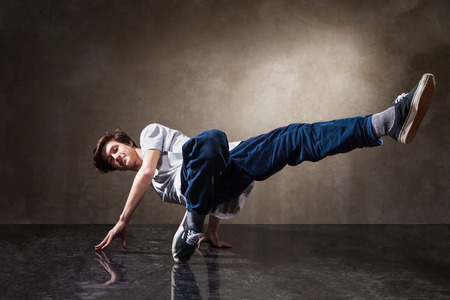 urban hip hop dancer with grunge concrete wall background texture jumping and dancing photo