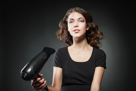 girl dries long hair by hairdryer over dark background. Conceptual photo photo