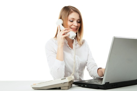Young professional business woman working at her desk with laptop and smiling while calling and having telephone conversation over white background. photo