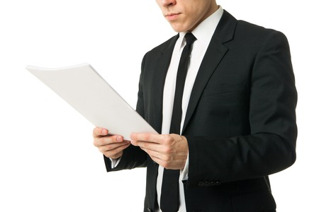young businessman reading papers from work isolated on white background Stock Photo - 27487105