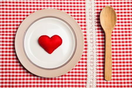 Plate with spoon on wooden table with red checked tablecloth and heart symbol photo