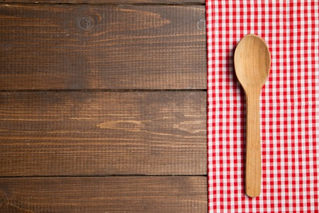 wooden spoon on table with red checked tablecloth photo