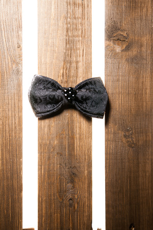 Black handmade bow tie over wooden background photo