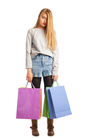 Portrait of young stressed woman surrounded by paperbags