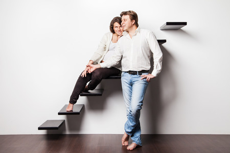 Couple at home sitting on stairs  Pregnant woman photo