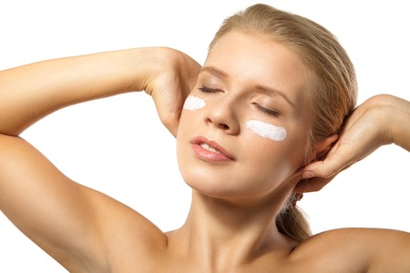 Portrait of young woman applying moisturizer cream on clean fresh face isolated photo