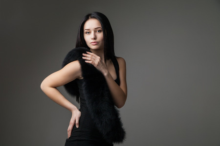 Beautiful Woman in Luxury Fur over gray background photo