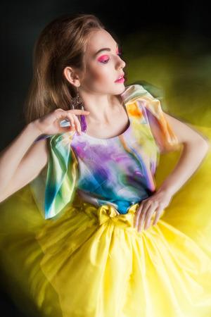 beautiful woman in long yellow dress posing dynamic in the studio photo