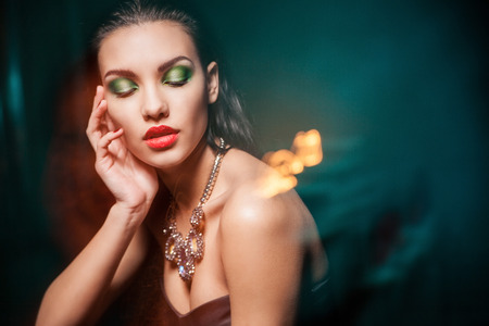 Beautiful woman with evening make-up over dark background  Jewelry and Beauty  Fashion photo photo