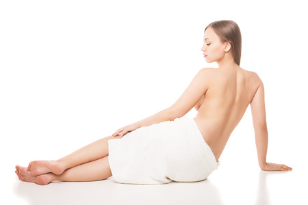 portrait of young beautiful woman wrapped in towel after bath sitting on the floor. Spa. Isolated over white background photo