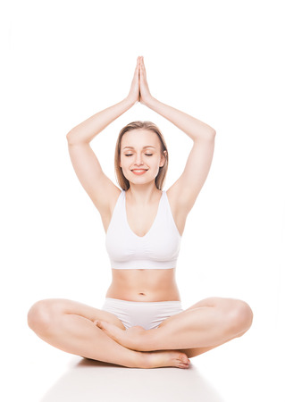 Young woman sitting in lotus position isolated over white background