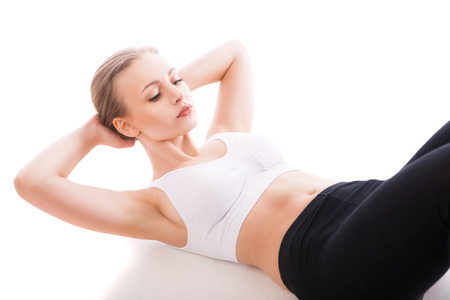 body care: picture of beautiful sporty woman doing exercise isolated over white background