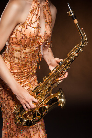 temptative: Portrait of sexual young woman posing with saxophone at studio.