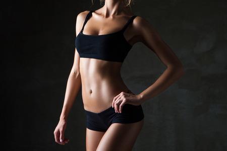 cuerpo femenino: El cuerpo de la mujer bronceada delgada sobre fondo gris oscuro
