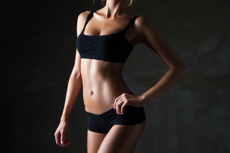 female body: Slim tanned womans body  over dark gray background