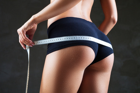 Woman measuring perfect shape of beautiful hips. Healthy lifestyles concept 스톡 콘텐츠