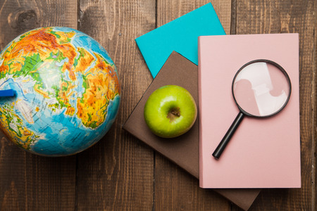 Globe, stack of books and magnifier on wooden background photo