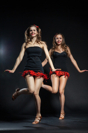 two cabaret dancers in bright costumes over dark background photo