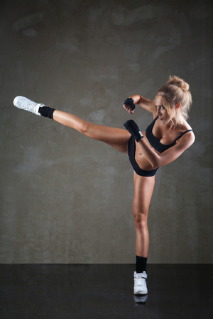 Beautiful girl kicking with the leg on dark grey background photo
