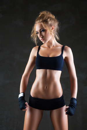 Healthy lifestyle and extreme sports. Beautiful fit woman model in black hand bandage photo